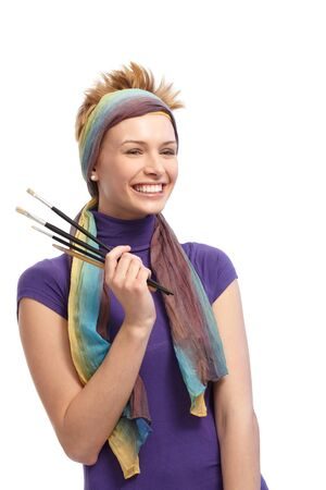 gingerish: Portrait of female painter with paintbrushes in hand, smiling happy.