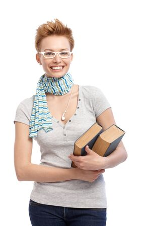 Gingerish femelles livres de détention étudiants, souriant à lunettes à montures blanches.