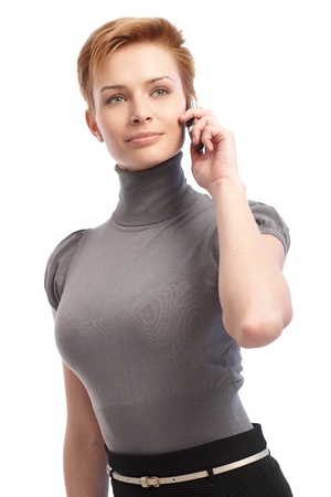 turtleneck: Pretty young businesswoman talking on mobile phone, looking away. Stock Photo