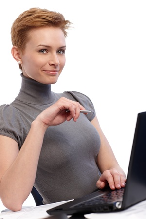 gingerish: Smiling young businesswoman working on laptop computer. Stock Photo