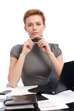Portrait of attractive young businesswoman thinking at desk, having laptop. photo