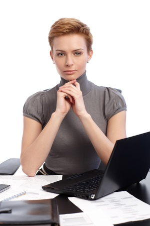 Portrait of attractive young businesswoman with short hair, sitting at desk, thinking. photo