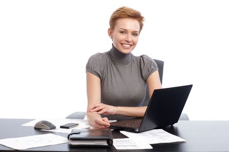 clothes organizer: Young businesswoman sitting at desk, working on laptop computer, smiling happy.