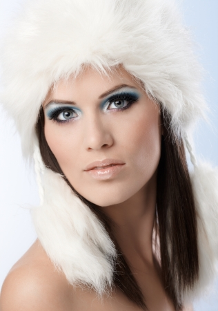 Winter beauty in fancy makeup and fur cap, looking at camera. photo