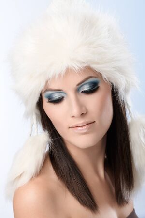 eyelids: Closeup portrait of winter beauty in fur cap and fancy makeup. Stress on eyelids and long lashes. Stock Photo