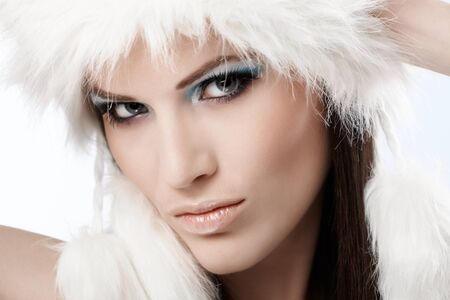 Winter portrait of beautiful young woman at wintertime in white fur cap. photo