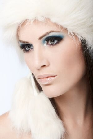 Closeup portrait of beautiful winter girl in fancy makeup and white fur cap. photo