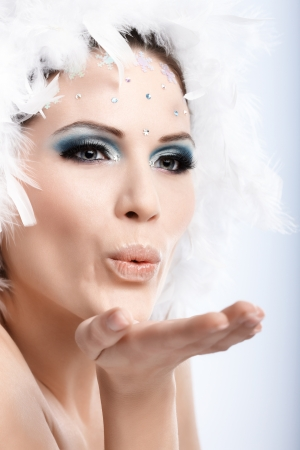 Winter beauty in professional makeup sending a kiss. photo