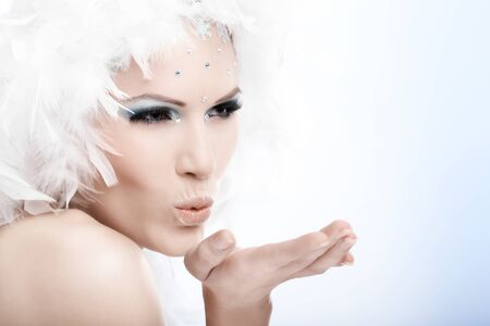 Winter beauty blowing a kiss, wearing white feather cap and fancy makeup. photo