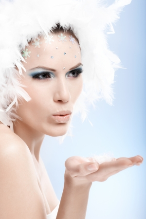 Beautiful woman in white feather cap and professional makeup makeup blowing a kiss in the air. photo