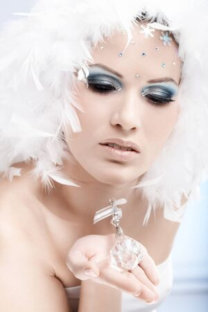 Portrait of winter beauty holding crystal gem, wearing professional makeup with strasses. photo