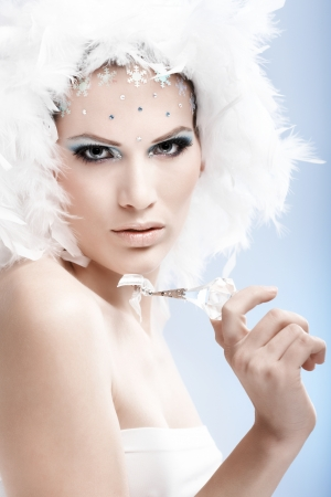 Luxurious winter beauty holding crystal gem, wearing professional makeup with rhinestones. photo