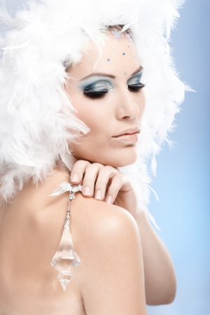 Luxurious beauty holding crystal jewel, wearing fancy makeup with strasses and white feather hat. photo