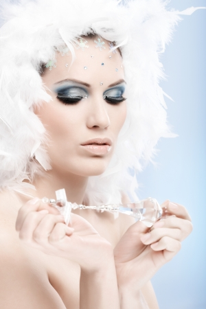 Artistic photo of beautiful winter girl holding crystal gem, wearing fancy makeup with strasses and white feather hat. Looking down. photo