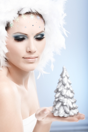 Beautiful woman in fancy makeup and white feather cap holding a small christmas tree in hand. photo