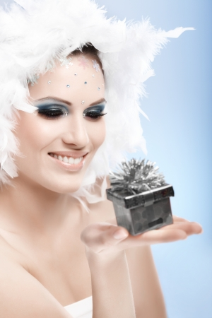 make a gift: Smiling winter beauty holding small present box, wearing feather hat and fancy makeup.