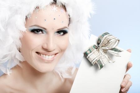 levantandose: Sonriendo belleza del invierno que sostiene regalo de Navidad, el uso de maquillaje de fantasía y sombrero de pluma blanca.