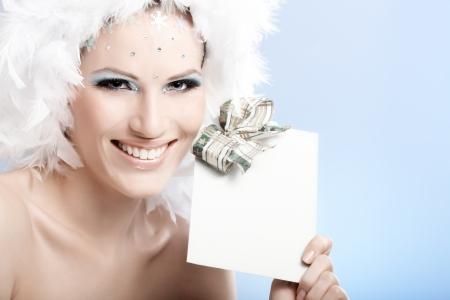 levantandose: Mujer feliz en el maquillaje de invierno y sombrero de plumas que sostiene fantasía regalo de Navidad.