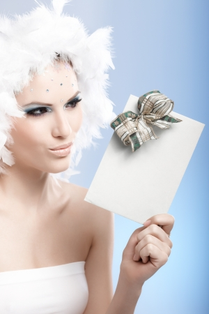 Beautiful woman in luxurious winter makeup and feather cap holding christmas present, looking at it curiously. photo