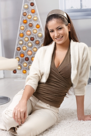 Happy young woman sitting on cosy living room floor at christmas, design decoration. photo