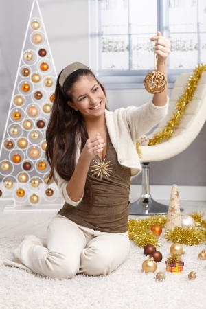 hairband: Laughing young woman preparing for christmas, selecting decoration design christmas tree in bright living room. Stock Photo
