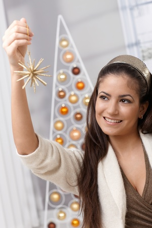 decorating christmas tree: Happy woman holding christmas decoration star, smiling, looking festive.