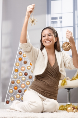 holding a christmas ornament: Happy pretty woman decorating for christmas, holding bulb and star, laughing, sitting in festive living room.