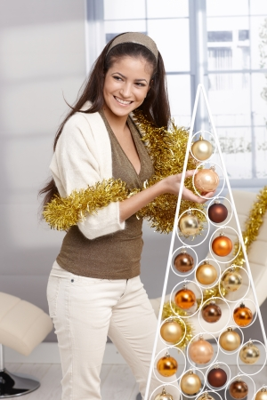 Laughing beauty decorating modern and design christmas tree with bulb, holding garland, smiling, looking away. photo
