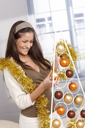 Laughing young woman doing design christmas decoration, garland and stylish modern tree. Stock Photo - 15286986