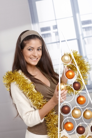 Happy beauty putting up christmas decoration, bulb, garland, modern style, smiling. Stock Photo - 15286985