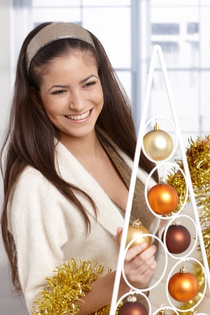 Christmas portrait of happy beauty decorating with bulb and garland, smiling. Stock Photo - 15286984