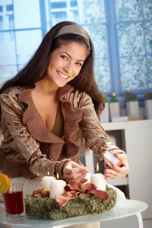 holiday lighting: Portrait of happy young woman lighting candle on advent wreath, christmas preparation. Stock Photo