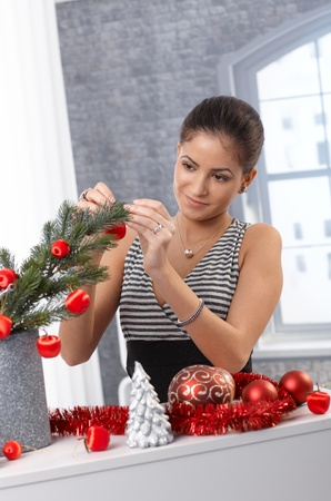 Smiling beauty decorating tree for christmas with red bulb and garland. photo