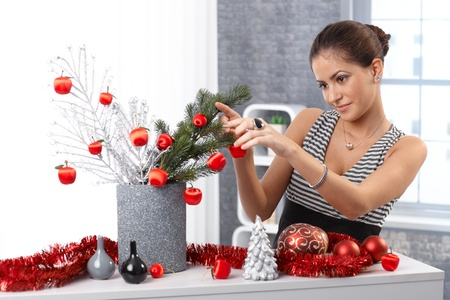 Portrait of young woman making christmas decoration at home, using stylish red bulb and garland, smiling. photo