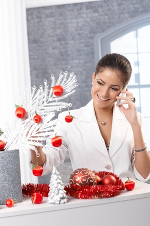 Portrait of smiling elegant woman talking on mobile phone decorating for christmas. Stock Photo - 15286895