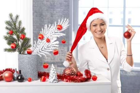 Happy woman smiling in Santa Claus hat, with christmas decoration, red bulb handheld. photo