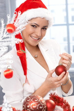 Happy christmas portrait, attractive woman in santa Claus hat smiling, decorating with ornament handheld. photo