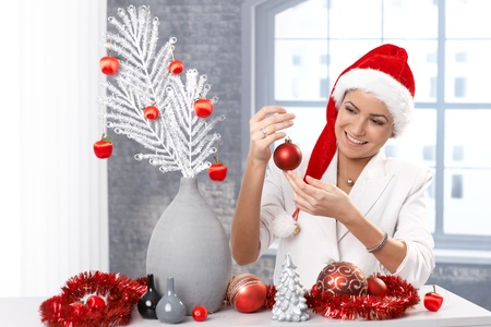 Happy woman getting ready for christmas, decorating home, wearing Santa Claus hat. photo