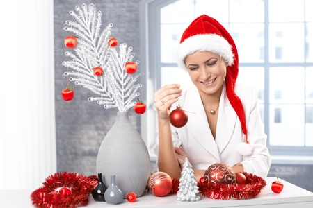 Portrait of smiling woman in Santa Claus hat decorating home for christmas with festive ornaments. photo