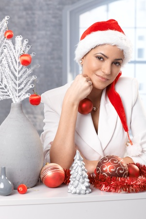 Smiling woman in Santa Claus hat daydreaming while decorating for christmas. photo