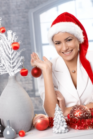 Portrait of attractive laughing woman in Santa hat preparing decoration for Christmas. photo