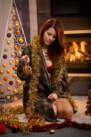kneel down: Sexy christmas portrait of attractive woman in dressing gown and red bra, decorating cosy living room for christmas.
