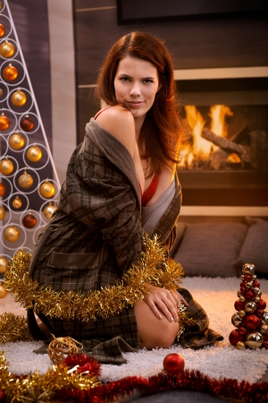 Sexy woman posing in bra and dressing gown at christmas tree and decoration in cosy living room with fireplace. photo
