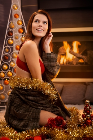 Portrait of hot girl smiling, posing in red bra and dressing gown surrounded with christmas decoration in front of cosy fireplace. photo