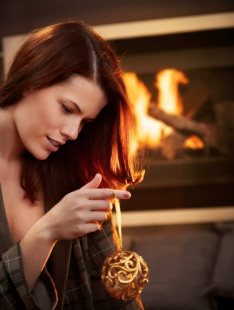 Beautiful young woman holding christmas bulb in front of fireplace. photo