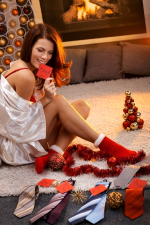 Sexy woman in silk gown and christmas socks arranging christmas gifts, tie with name tag for men. Stock Photo - 15287074