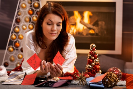 decorating christmas tree: Smiling girl thinking to decide on christmas presents, arranging name tag with tie, lying in cosy living room in front of fireplace.
