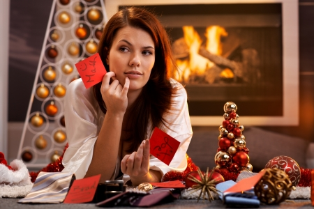Woman arranging christmas gifts by fireplace, holding gift tag with male names, thinking, smiling, looking aside. photo