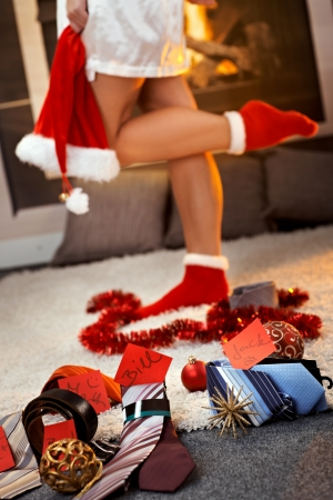 Christmas gifts of tie, belt for men with name tag by pretty girl wearing christmas socks and Santa hat by fireplace. photo