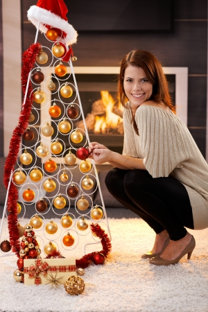 to crouch: Happy woman posing with design christmas tree with tinsel and bulb and Santa hat and gift, in cosy living room with fireplace.